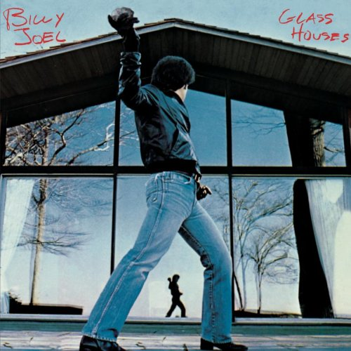 "This is the cover of Billy Joel's seventh studio album, titled ""Glass Houses."" This image illustrates the second interpretation of the idiom; the vulnerability of people who live in glass houses."